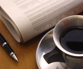 Showing pen, newspaper and coffee cup